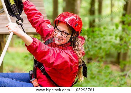Teenage child enjoying climbing on a high rope course
