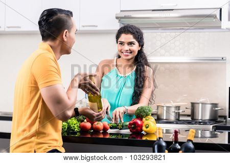 Indian woman and man in kitchen with red wine making salad