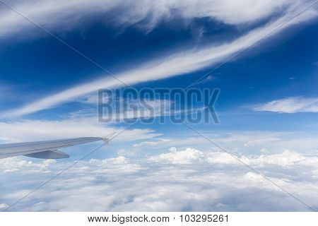 Wing Of The Airplane Flying Above The White Fluffy Clouds.