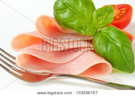 lean pork ham slice with cherry tomato, leaves of basil and fork