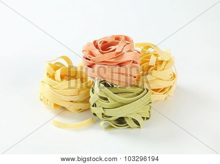 four pieces of green pink and yellow dry pasta