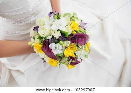 Woman in a white dress holding her wedding flowers