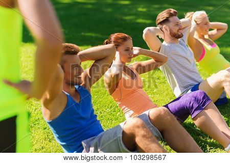 fitness, sport, friendship and healthy lifestyle concept - group of happy teenage friends or sportsmen exercising and doing sit-ups at boot camp
