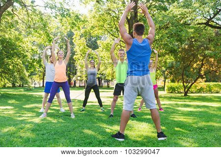 fitness, sport, friendship and healthy lifestyle concept - group of happy teenage friends or sportsmen exercising  at boot camp
