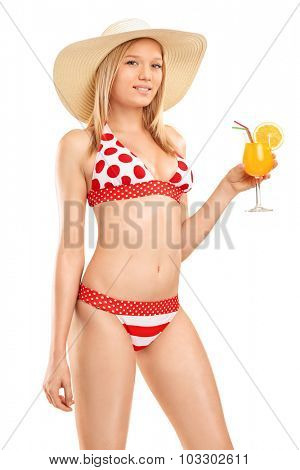 Vertical shot of an attractive woman in a red bikini holding a cocktail and looking at the camera isolated on white background