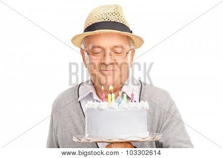 Senior gentleman blowing candles on a birthday cake isolated on white background