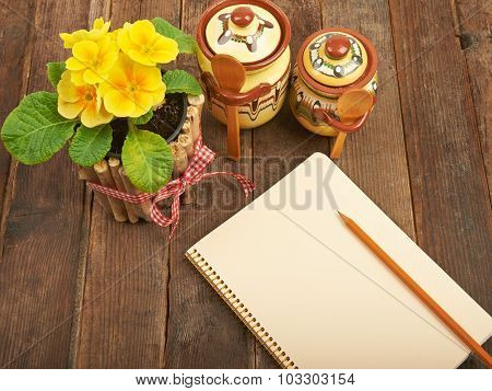 Notebook with a pencil on a wooden table with yellow primroses a