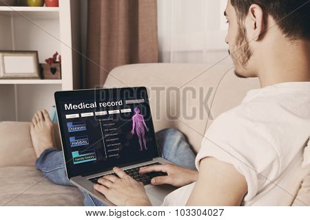 Handsome young man sitting on sofa and using laptop in room