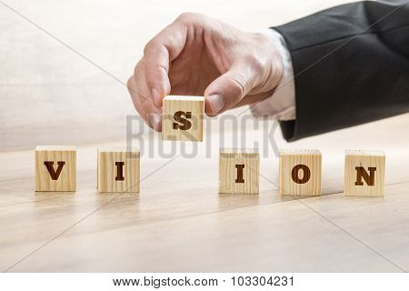 Closeup Of Business Manager Assembling A Word Vision With Six Wooden Cubes