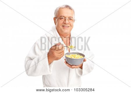 Joyful senior in a white bathrobe eating cereal from a bowl and looking at the camera isolated on white background