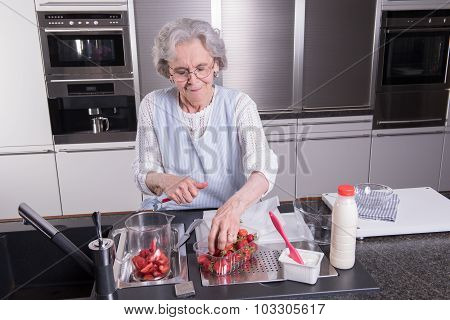 Active Female Pensioner Is Preparing And Eating Strawberries In The Kitchen