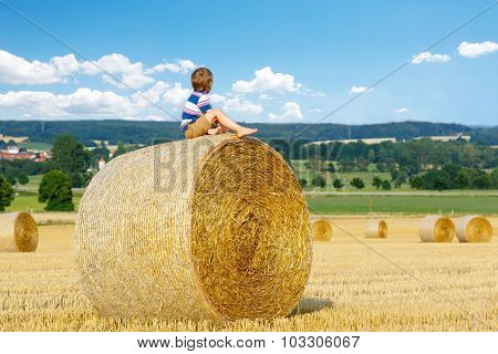 Little Kid Boy Sitting On Hay Bale In Summer