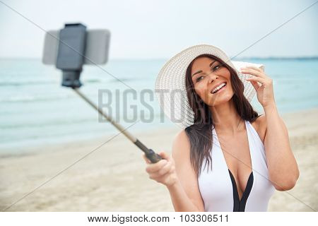 travel, leisure, summer, technology and people concept - sexy young woman taking selfie with smartphone on beach