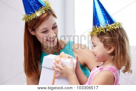 holidays, birthday family, childhood and people concept - happy mother and little girl in party caps with gift box at home