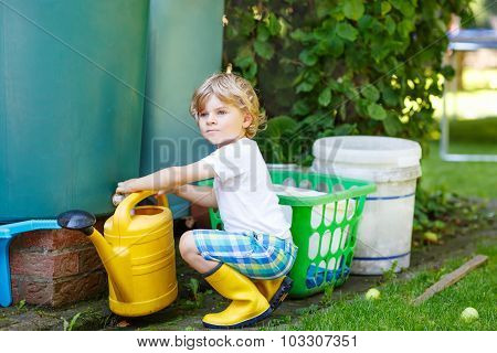 Little Kid Boy Watering Plants In Garden In Summer