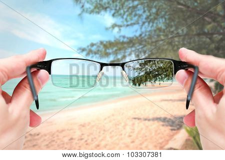 Female Hand Holding Glasses Focus Mirror Lens On Sand Sea Travel Trip.