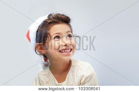christmas, holidays, childhood and people concept - happy little girl in santa hat over gray background