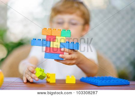 Little Kid Boy Playing With Plastic Blocks