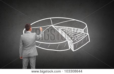 business, people, advertisement , information and office concept - businessman drawing pie chart from back over dark gray concrete wall background