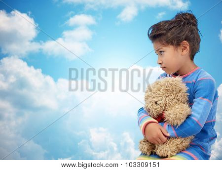 childhood, sadness, loneliness and people concept - sad little girl with teddy bear toy over blue sky and clouds background