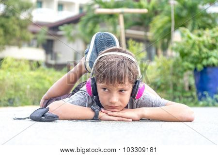 young caucasian boy listening to music via headset on natural background