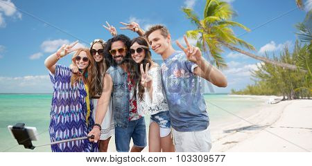 summer vacation, travel, technology and people concept - smiling young hippie friends in sunglasses taking picture by smartphone on selfie stick and showing peace gesture over beach background
