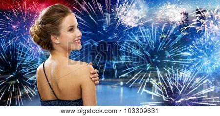 people, holidays and glamour concept - smiling woman in evening dress from back over nigh city and firework background
