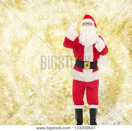 christmas, holidays, gesture and people concept - man in costume of santa claus with bag pointing finger up over yellow lights background