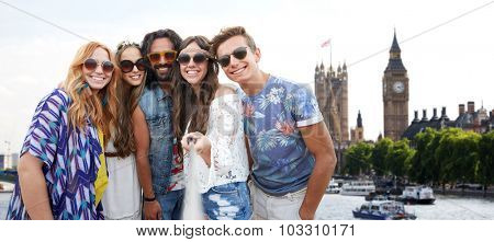summer vacation, travel, tourism, technology and people concept - smiling young hippie friends taking picture by smartphone selfie stick over big ben tower in london city background