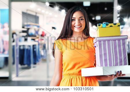 Beautiful young woman with shopping boxes in the mall