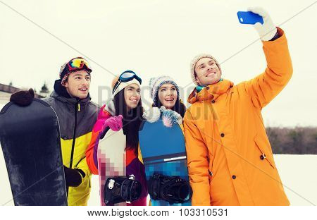 winter sport, leisure, friendship, technology and people concept - happy friends with snowboards and smartphone taking selfie