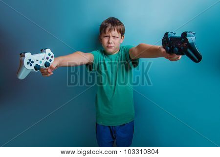 Teen  boy of twelve European  appearance holds a  gaming zhdoyst