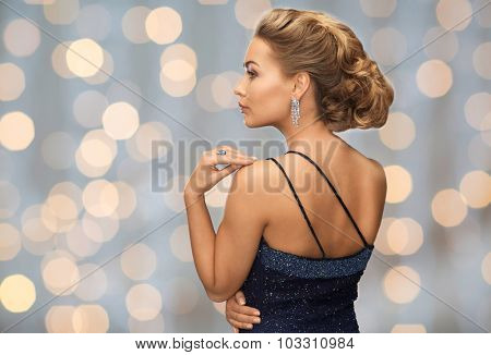 people, holidays, christmas, jewelry and glamour concept - beautiful woman with diamond earring over lights background