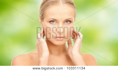 beauty, people and health care concept - beautiful young woman touching her neck over green natural background