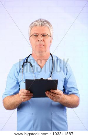 Doctor with clipboard on light blue background