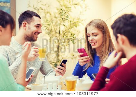 people, leisure, friendship and technology concept - group of happy friends with smartphones meeting at cafe and drinking tea