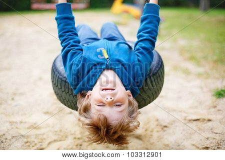 Little Kid Boy Having Fun On Swing In Summer