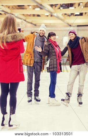 people, friendship, technology and leisure concept - happy friends taking photo with smartphone on skating rink