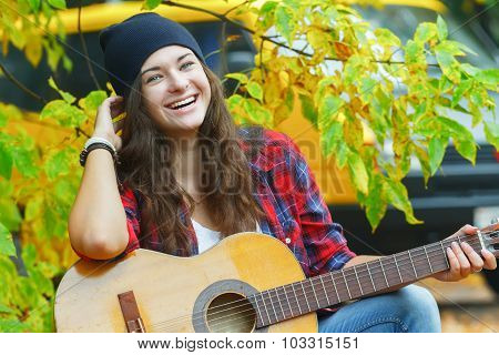 Portrait Of Laughing Guitar Player Girl Squatting At Yellow Van And Autumn Tree Leaves Background