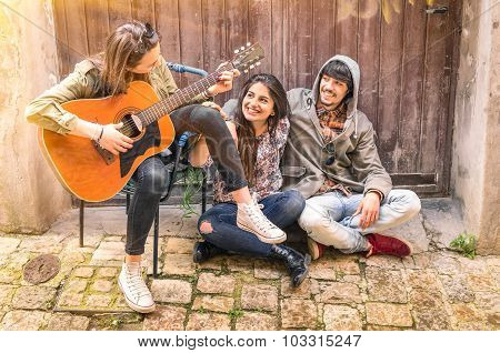 Group of teenager friends having fun playing Guitar