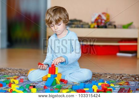 Little Blond Child Playing With Colorful Wooden Blocks Indoor