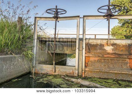 gates (headgates) and foot bridge of irrigation ditch, summer in Colorado farmland