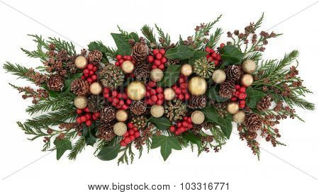 Christmas gold bauble decorations, holly, mistletoe, ivy, pine cones and traditional greenery over white background.