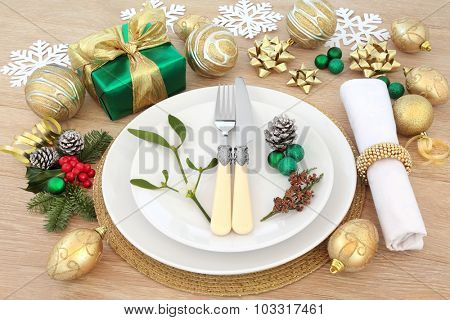 Christmas dinner place setting with plates, napkin, gold baubles, gift box, holly, mistletoe and fir over light oak background.