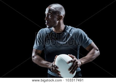 Determined rugby player holding ball while looking away against black background