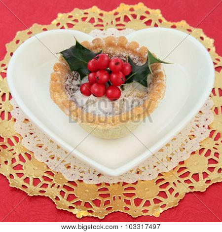 Mince pie fruitcake and holly on a gold doilie on a heart shaped plate over red background.