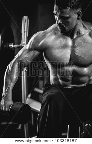 Brutal athletic man pumping up muscles with dumbbells in monochrome