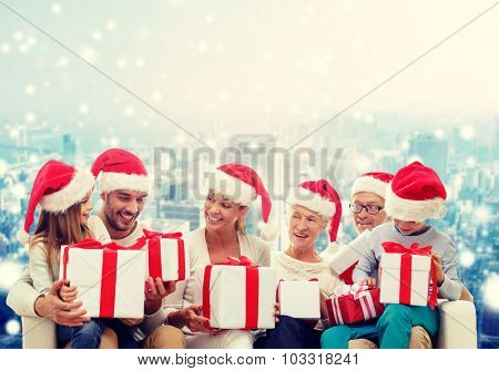 family, happiness, generation, holidays and people concept - happy family in santa helper hats with gift boxes sitting on couch over snowy city background