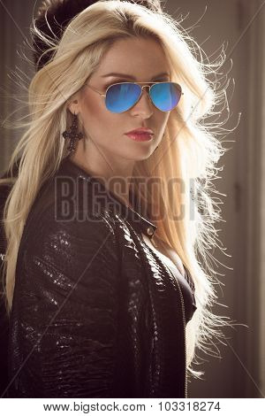 Portrait of a sexy blond woman in blue sunglasses