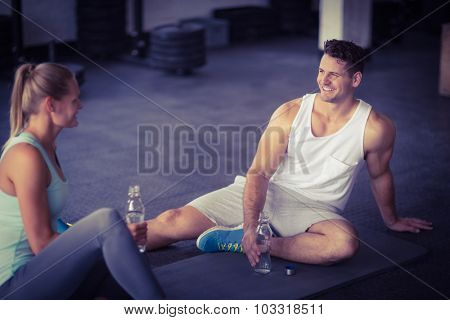 Sitting young couple drinking water together in crossfit gym
